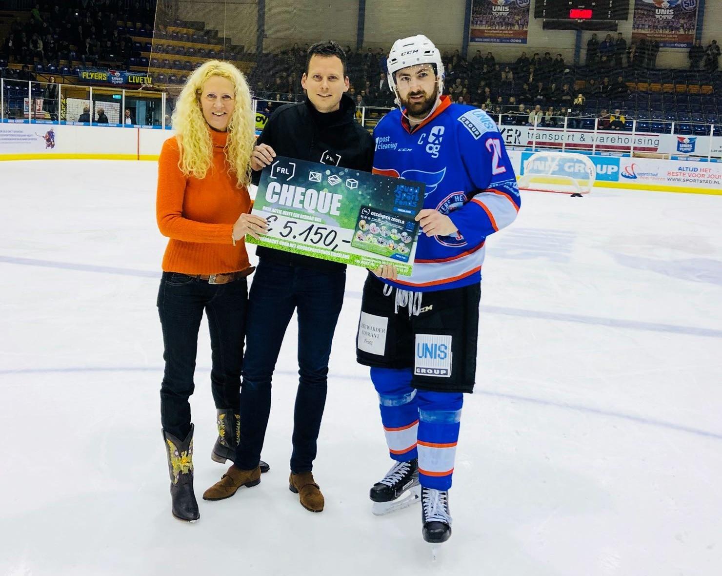 Ambassadeur Jeugdsportfonds Friesland Tony Demelinne neemt cheque in ontvangst.